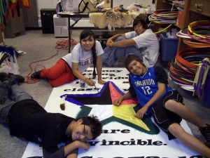 Native American kids painting a banner.