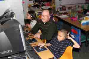 Fr. Steve and two Native American students working on the computer.