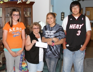 Cansas, Janis and Adrian presented Carol Riggins, director of the Missouri Valley Crisis Center, a check from the proceeds of the dance.