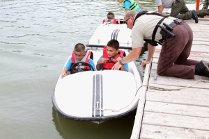 Two Native American boys learning about a boat!