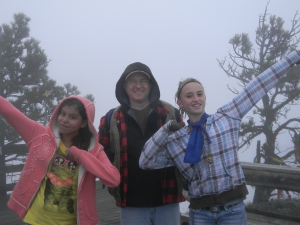 Two girls and Fr. Steve at the top of Bear Butte.
