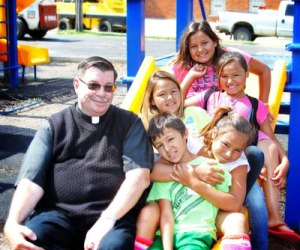 Fr. Anthony takes a break on the playground with the Lakota children.