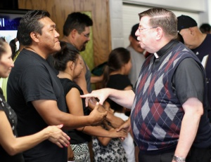 Fr. Anthony shakes hands with members of the Black Lodge Singers after their presentation at St. Joseph's Indian School.