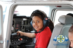 Young boy sits in cockpit of plane.