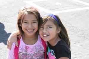 Two girls hug on the playground