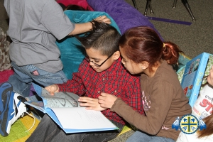 Two Lakota students sit on the ground reading a book.