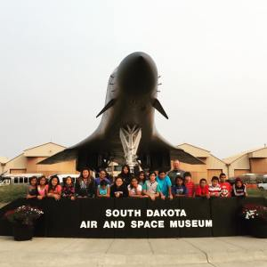 Our Lakota (Sioux) students stand behind the Air & Space Museum sign during their field trip.