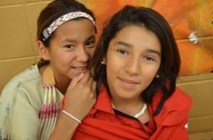 Two Lakota(Sioux) girls dressed in regalia await their turn.
